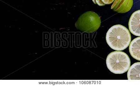 Green lemon slices on a black wooden surface. Background. Free space for a text