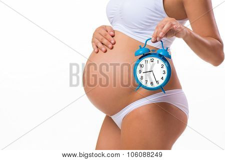 Happy Pregnancy. Pregnant Belly With Alarm Clock. Conceptual Image. Soon Birth. Fetal Development