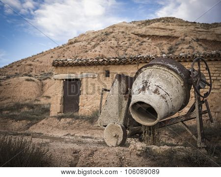A rusty brown Cement Mixer and an old house