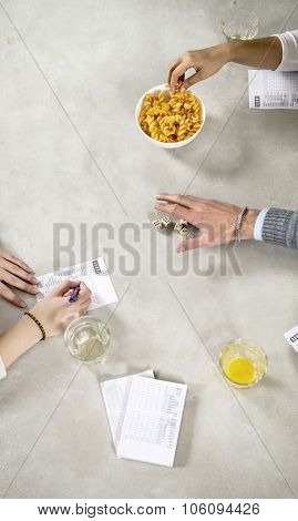 Several hands on a concrete table top during a game of dice, with a score block, glasses with drinks, noting down scores, reaching for the dice or taking crisps from a bowl.
