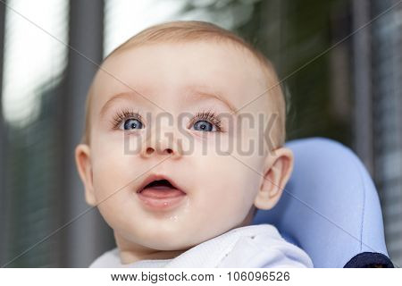 Adorable baby sitting in chair and looking up