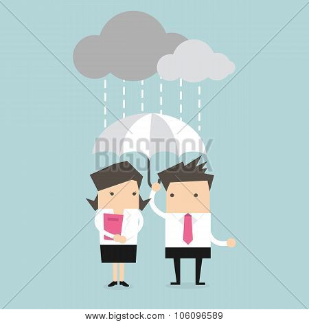 Businessman & businesswoman under umbrella in the rain