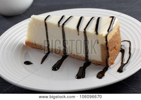 Slice of cheesecake with liquorice sauce on a plate closeup