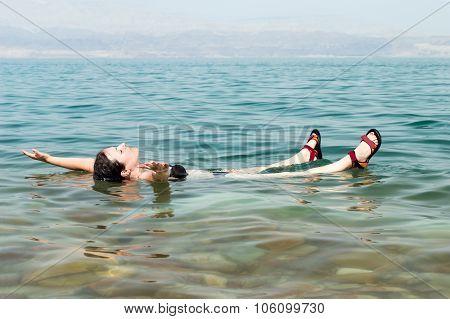 Woman Floating In Water Of Dead Sea