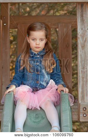 little girl wearing a denim jacket sitting on top of a slide