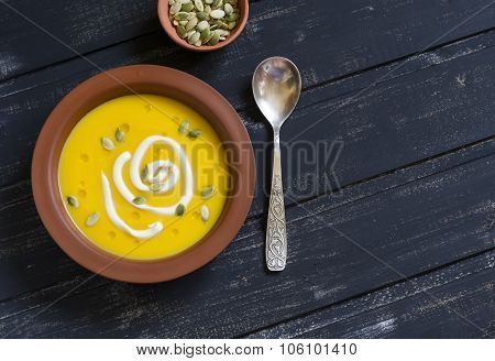Pumpkin Soup In A Clay Bowl On A Dark Wooden Surface