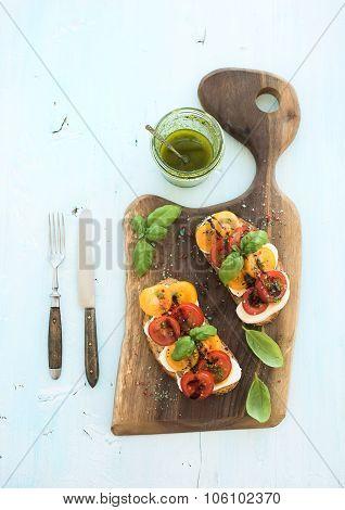 Tomato, mozzarella and basil sandwiches on dark wooden chopping board, pesto jar, dinnerware over li