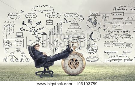 Young handsome businessman sitting in chair with cup in hands and his legs on watch