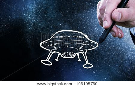 Person hand drawing UFO ship on space background