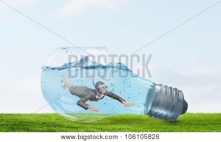 Young businesswoman in suit and diving mask jumping in lightbulb with water