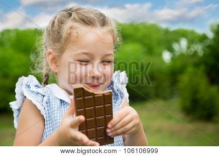 Joyful girl eating chocolate in the park.
