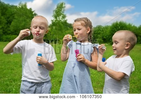 Happy brothers and sister inflate soap bubbles outdoors in park