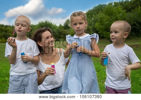 Mother and child blowing soap bubbles in summer park