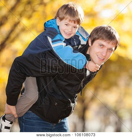 Happy father and his son in the autumn park