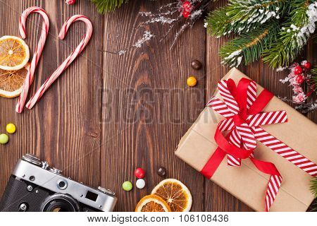 Christmas background with gift box, camera and fir tree branch