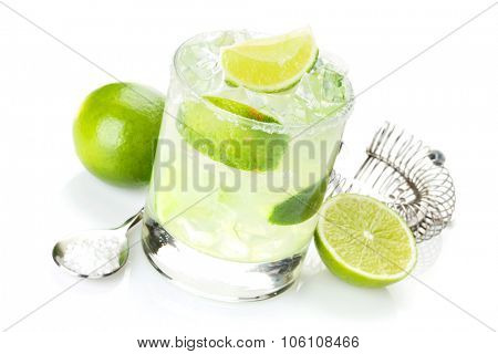 Classic margarita cocktail with salty rim, limes and drink utensils. Isolated on white background