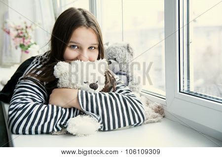 Girl In A Striped T-shirt Hugging A Teddy Bear Lying On The Windowsill