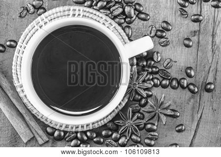 Coffee On The Cup With Coffee Beans And Cinnamon Sticks On Wood Background On Black And White, Selec