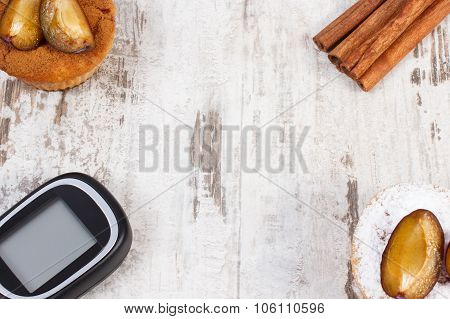 Glucometer, Muffins With Plums And Cinnamon Sticks On Wooden Background, Copy Space For Text