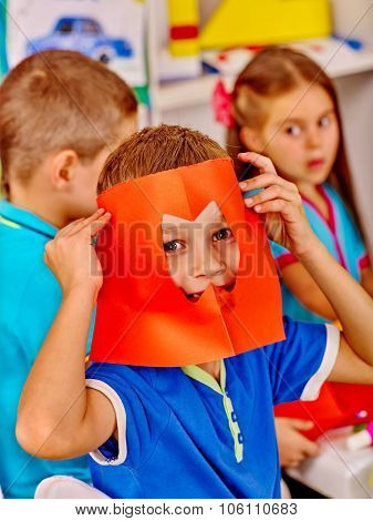 Group kids holding colored paper on table in kindergarten .