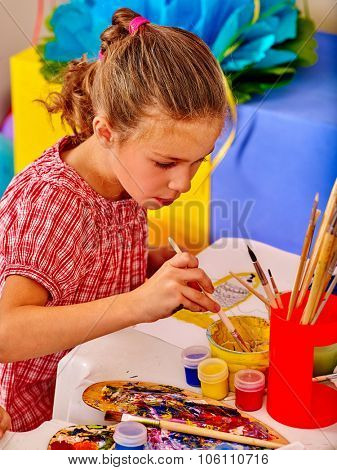 Little girl  painting child picture on desk in kindergarten .