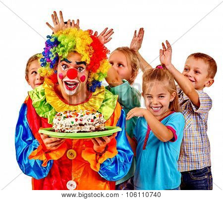 Clown wearing wig and costume  holding cake on birthday with group children. Isolated.