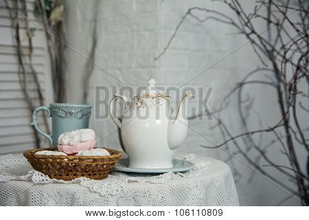 A Table Covered With Thick Cloth With A Cup Of Tea And Tea And Marshmallow In A Wicker Plate