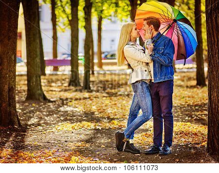 Happy young couple full height kissing under umbrella in autumn day. Love and couple relationships concept .