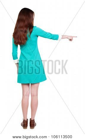 Back view of  pointing woman. beautiful girl. Rear view people collection.  backside view of person.  Isolated over white background. The girl in a blue dress with brown boots in shows to the left ..