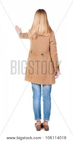 back view of woman. Young woman in cloak presses down on something. Isolated over white background. Rear view people collection. backside view of person. she holds his hand open, palm forward