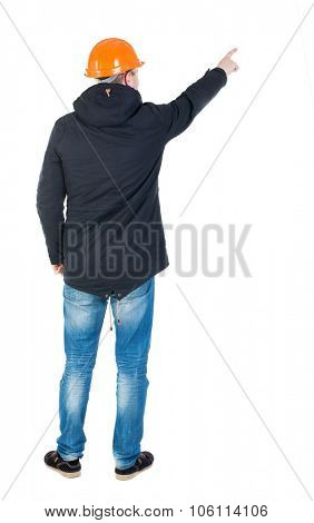 Back view of  pointing young men in parka and helmet. Young guy  gesture. Rear view people collection.  backside view person.  Isolated over white background. Young engineer specifies the left hand