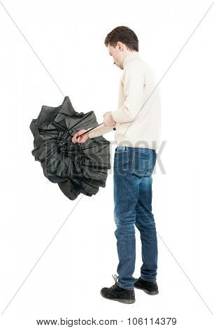 Back view of man in jeans  with umbrella. Standing young guy. Rear view people collection.  backside view of person.  Isolated over white background. A guy in a white warm sweater folded umbrella.