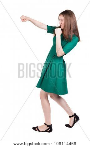 skinny woman funny fights waving his arms and legs. Isolated over white background. A girl in a long green dress boxing.