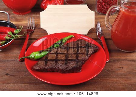 red theme lunch fresh grilled bbq roast beef steak red plate green chili tomato soup ketchup sauce paprika glass ground pepper american peppercorn modern cutlery served wooden table empty nameplate