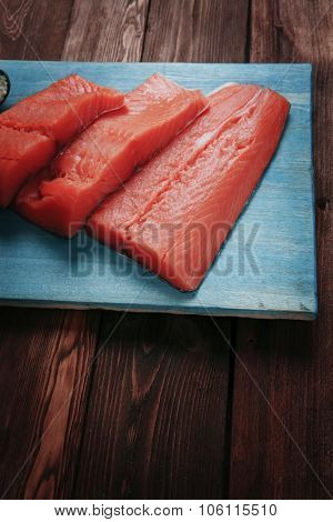 fresh raw salmon fillet served with lemon and white wine in wineglass bottle wooden barrel on blue plate over vintage wood table with forged handmade cutlery knife and 