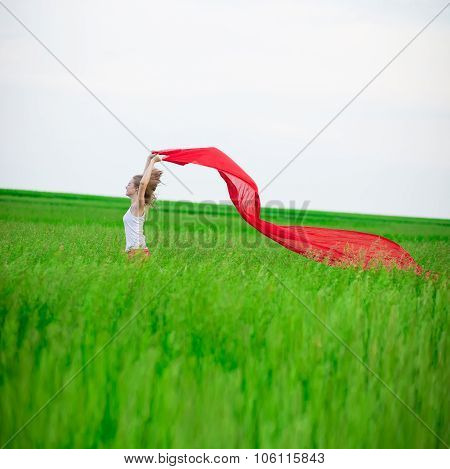 Young lady running with tissue in green field. Woman with scarf.