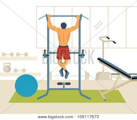 Man pull-up up on horizontal bar in gym.