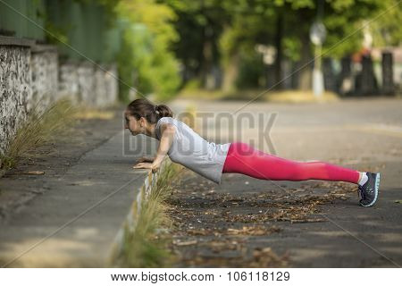 Young athletic woman doing push-ups outdoors.