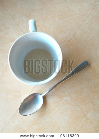 Teacup and spoon on the stone table.