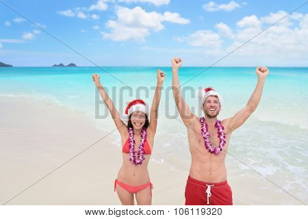 Happy Christmas holiday - multiracial joyful couple cheering arms up on Hawaii beach for their winter vacation during new year.