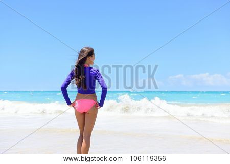 Beach woman in rash guard living an active lifestyle. Healthy young adult standing looking at waves before swimming wearing sun protective long sleeves swim shirt as solar protection against uv rays.