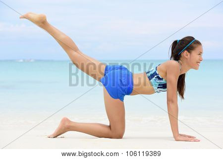 Kneeling leg lift butt toning exercise - Asian fitness woman working out on beach in blue sports bra and shorts strength training her glutes with pilates rear raised legs and donkey kick exercises.
