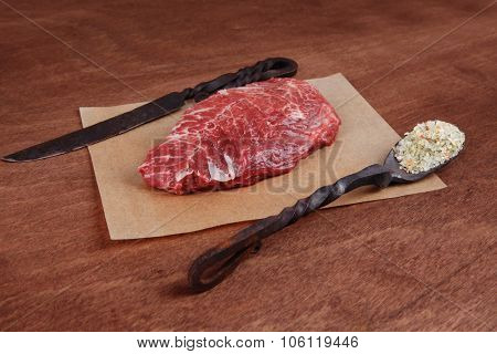 fresh raw beef rib eye steak on walnut table with salt spice and black iron antique forged cutlery fork knife