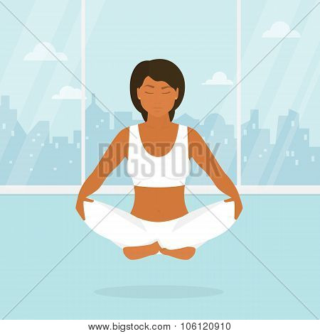 Woman is doing yoga and sitting in the lotus position