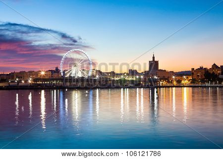 Sunset Cityscape With Ferris Wheel In Motion. Malaga City, Spain.