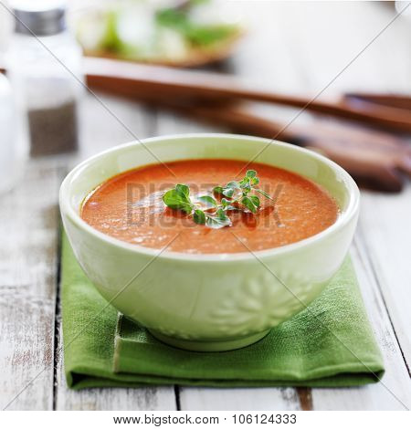 tomato soup with herb garnish in green bowl