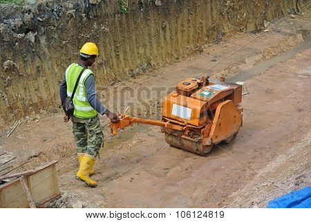 Construction workers using baby roller compactor