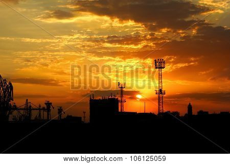 Bright Sunset  And Black Silhouettes Of Buildings And Seaport Cranes