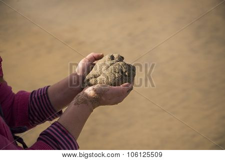 Child holding a sand heart, cornwall, uk