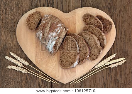 Rye bread sliced loaf on a heart shaped wooden board with wheat sheaths over old oak background.
